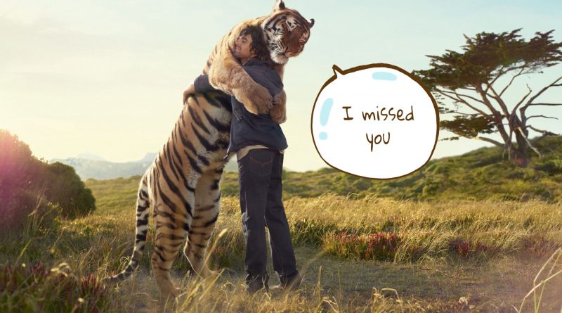 A man hugging his huge tiger friend
